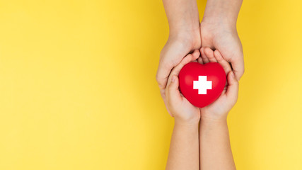 world red cross day, adult and child hands holding red heart, healthcare, love and family insurance concept Fototapete