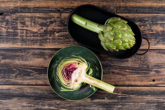 Artichoke and slice in a pot and plate with top view on a dark wooden background