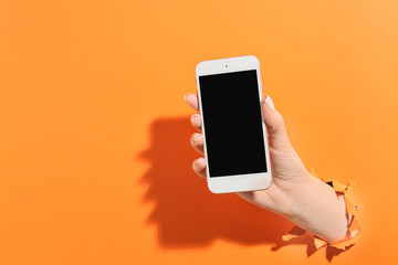 Female hand with mobile phone on color background