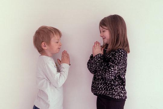 children performing namaste greetings in time of coronavirus pandemic outbreak