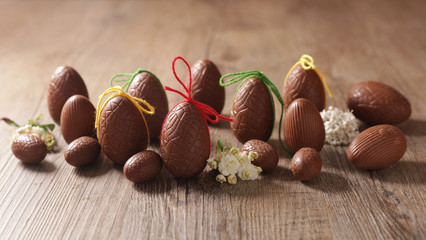 chocolate easter egg and bow on wood background