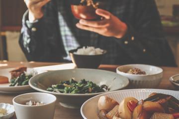 男性が味噌汁茶碗を持つ食事風景