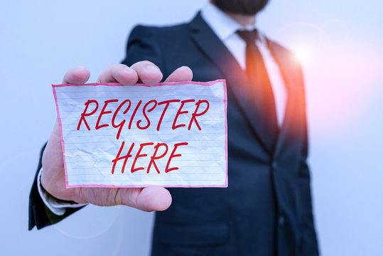 Writing note showing Register Here. Business concept for put your name on an official list in order to receive service Male human wear formal work suit with office look hold book