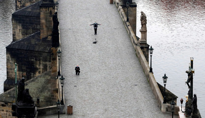 People take pictures on an empty medieval Charles Bridge in Prague