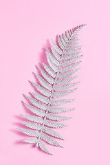 fern leaf in glitter sequins. simple minimalistic composition on a pink background. top view, vertical frame