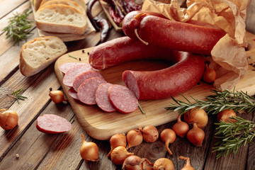 Wall Mural - Smoked sausage with bread and spices on a old wooden table.