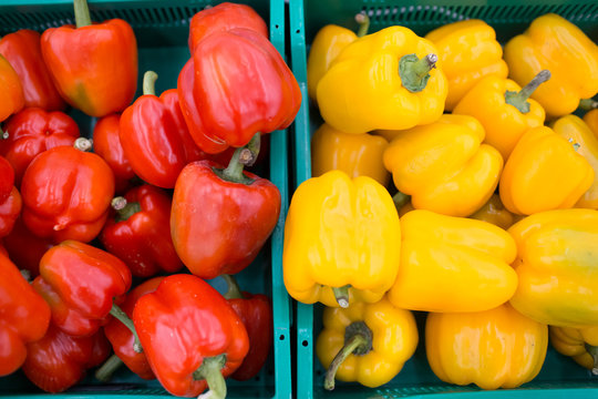 Red and yellow bell peppers on a store counter