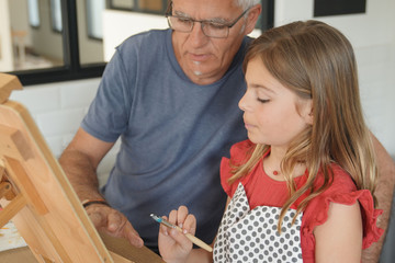 a father with his daughter painting