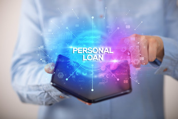 Businessman holding a foldable smartphone with PERSONAL LOAN inscription, new business concept