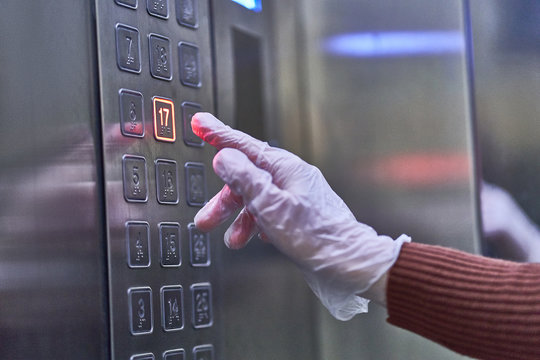 Person in transparent rubber protective gloves presses the elevator button. Protection against viruses, germs and bacteria