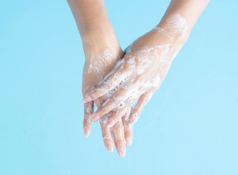 Closeup woman's hand washing with soap on blue background, health care concept