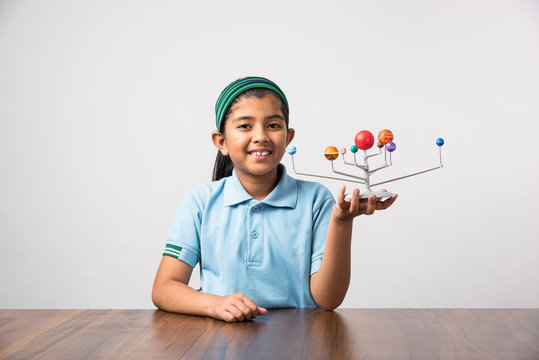 Indian Schoolgirl / girl child studying Planets or planetary science with 3d Model of our solar system