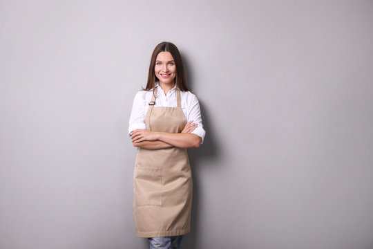 Young woman in an apron on a gray background.