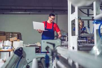 Fototapeta Industrial engineer with laptop in a  industrial manufacture factory working.