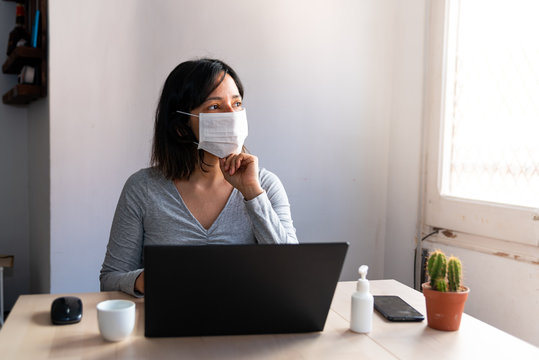 young woman wearing protective face mask and with hand sanitizer in home office looking worried and stressed out of the window due to corona virus