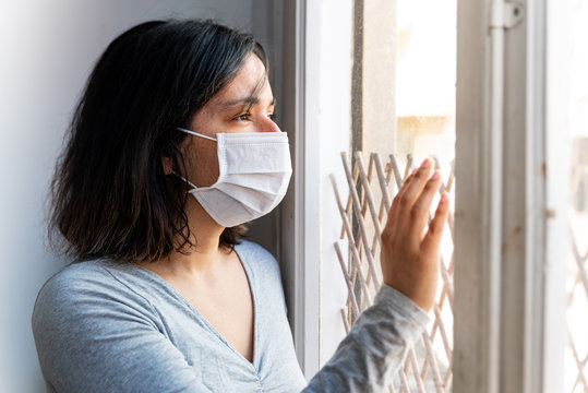 portrait of young woman infected with corona virus with face mask looking out of window while in quarantine with sad and worried expression due to isolation