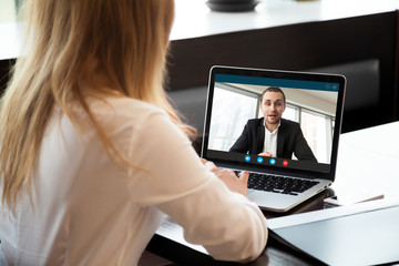 Businesswoman making video call to business partner using laptop, looking at screen with virtual...