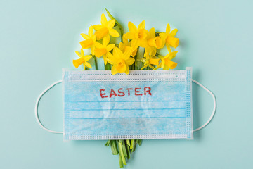 Easter time in quarantine concept. Face medical mask on narcissus flowers on blue background. flat lay