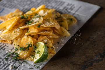 selective focus of potato chips with salt near sliced lime and newspaper on marble surface
