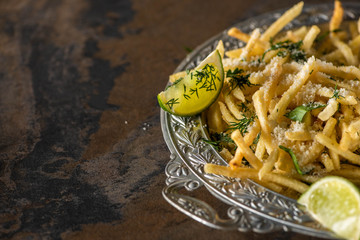 selective focus of salted french fries and sliced lime on marble surface