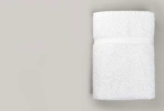 Top view of folded clean white bathroom towel on gray background with copy space