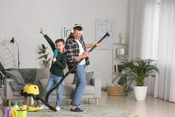 Little boy and his father having fun while hoovering floor in room