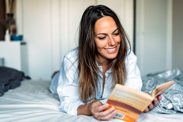 Happy young woman lying on bed reading a book