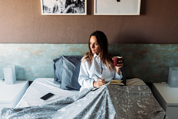 Smiling female with diary in bed with hot beverage