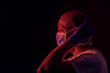 Coronavirus, side portrait of african american man putting on a protective mask. COVID-19 concept. Studio shot with red light on dark background with copyspace