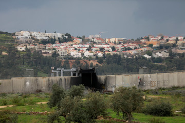 A view shows the Jewish settlement of Modiin Illit in the background and the Israeli barrier in the foreground, in the village of Bilin in the Israeli-occupied West Bank