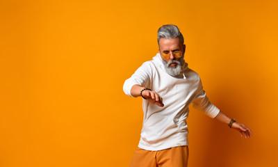 Studio shot of modern, hipster businessman pretends dancing, isolated on orange background