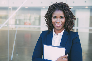 Happy friendly legal expert posing outside. Young black business woman standing at glass wall,...