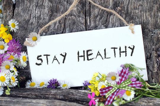 Stay Healthy als Schriftzug auf weisser Tafel mit Blumen in der Natur