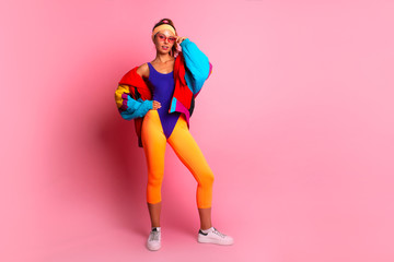 Full length image of 80's Fashion woman over pink background. Beautiful athletic girl in 80s style sportswear, fashionable woman in bright body suit  Wall mural