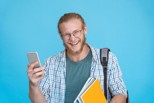 Cheerful young man millennial male student user hold phone looking at camera laughing at funny social media content having fun with mobile gadget isolated on blue studio background, portrait.