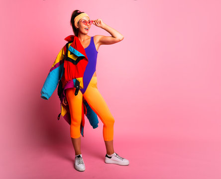 Full length fashion portrait of young trendy woman in cap and jeans looking away.young and cool, hipster girl with colored coat, orange leggings  and body suit. 80s 90s style