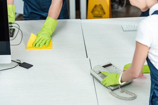 partial view of cleaner wiping office phone near colleague washing desk