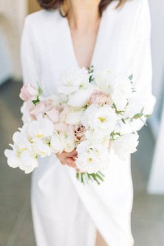 Floristics in the style of fine art in Europe. Light bouquet of peonies and roses. Modern wedding bouquet in the hands of the bride.