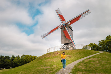 Foto auf Leinwand Brugge Brugge Belgium, colorful house at the old city of Brugge , young woman free in the city by the old windmill,Bruges, Belgium. Sint Janshuismolen wind mill dating from 1770, still in its original spot