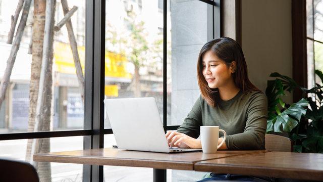 Beautiful asian woman using laptop at cafe