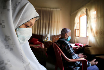 Ahmad al-Asmar, 84, and his wife Nouzat Awada, 79, perform Friday prayers inside their home as mosques are closed over concerns of the spread of coronavirus disease (COVID-19) in Sidon