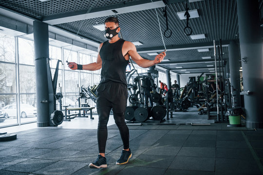 Strong young man in sportive clothes and scary mask doing exercise by using jump rope in gym