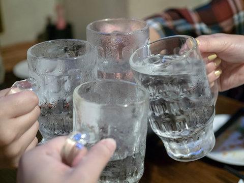 沖縄の居酒屋で泡盛のジョッキで乾杯をする