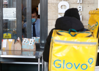 A McDonald's employee wearing a protective face mask looks out as a Glovo food delivery courier picks up an order outside a restaurant in central Kiev