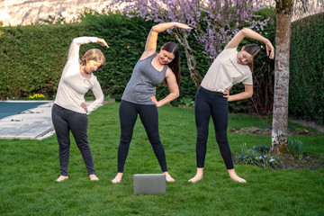Family practicing fitness lesson online outdoors in garden at quarantine isolation period during coronavirus pandemic. Doing sport together at home via skype. Healthy active lifestyle