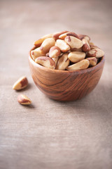 Brazil nuts in wooden bowl on wood textured background. Copy space. Superfood, vegan, vegetarian...