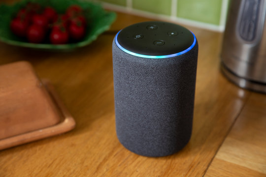 BATH, UK - MARCH 20, 2020 : Close up of a 3rd generation Amazon Echo smart speaker glowing blue on a kitchen worktop