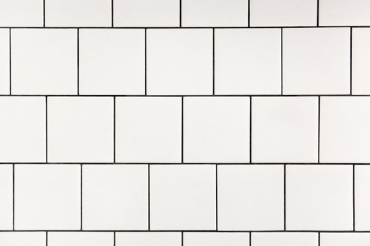 White square ceramic tile with black seam, located horizontally. Abstract background, ceramic texture.