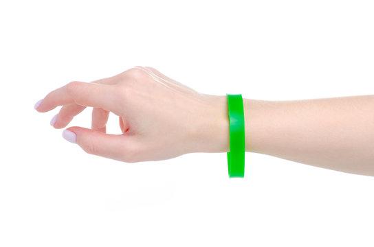 Green rubber bracelet on hand on white background isolation