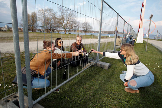 Friends clink with beer bottles through a fence built by German authorities on the German-Swiss border, as a protection measure due to the spread of the coronavirus disease (COVID-19), in an park on the banks of Lake Constance in Kreuzlingen